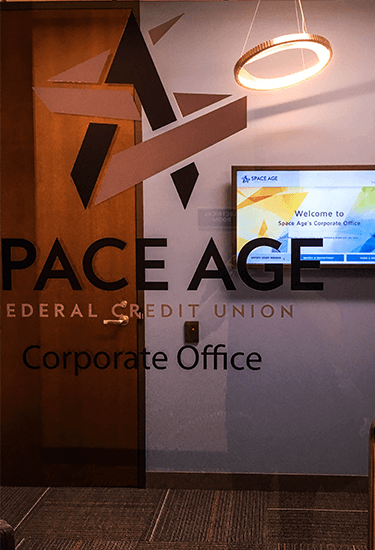 "A window with ""Space Age Federal Credit Union"" and a welcome signage screen in the background"