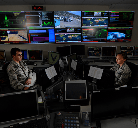 Two United States military soldiers using computers in an intel computer room