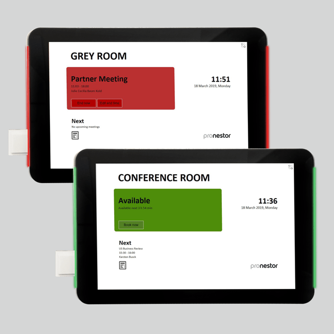 Two IAdea tablets displaying corporate meeting room information on a wall