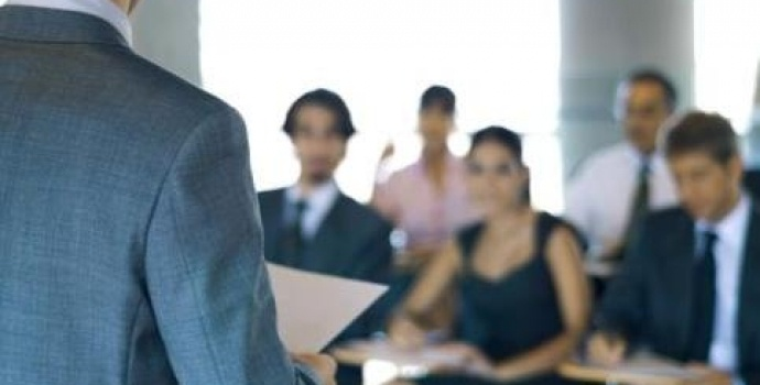 Over-head shot of businessman speaking with an audience about digital signage training