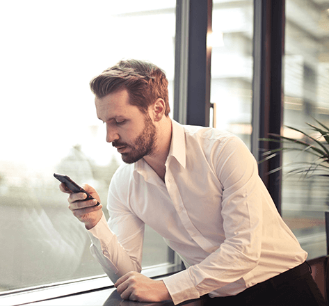 Image of business individual holding a phone by a window