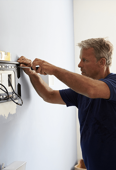 Image of a person installing TV at the wall