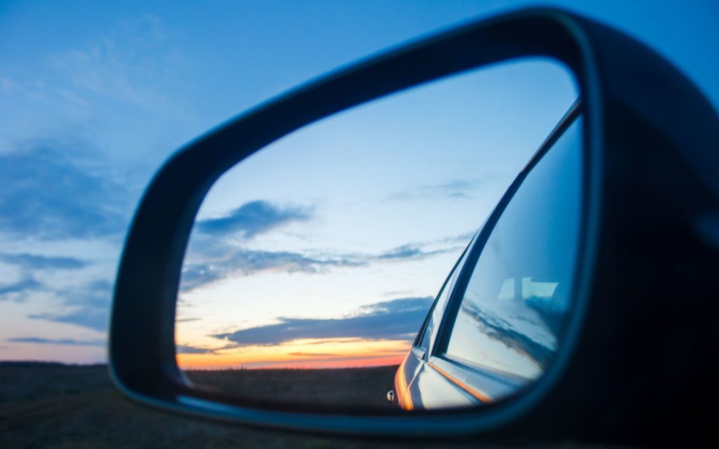 close-up of a rearview car mirror showing the sunset on the horizon