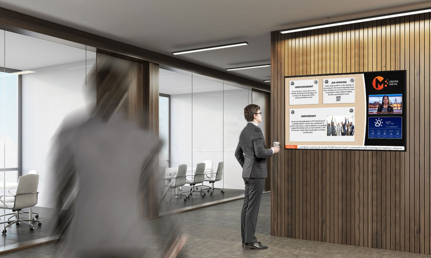 a lobby room with a man holding a cup of coffee and looking at a digital display on the wall
