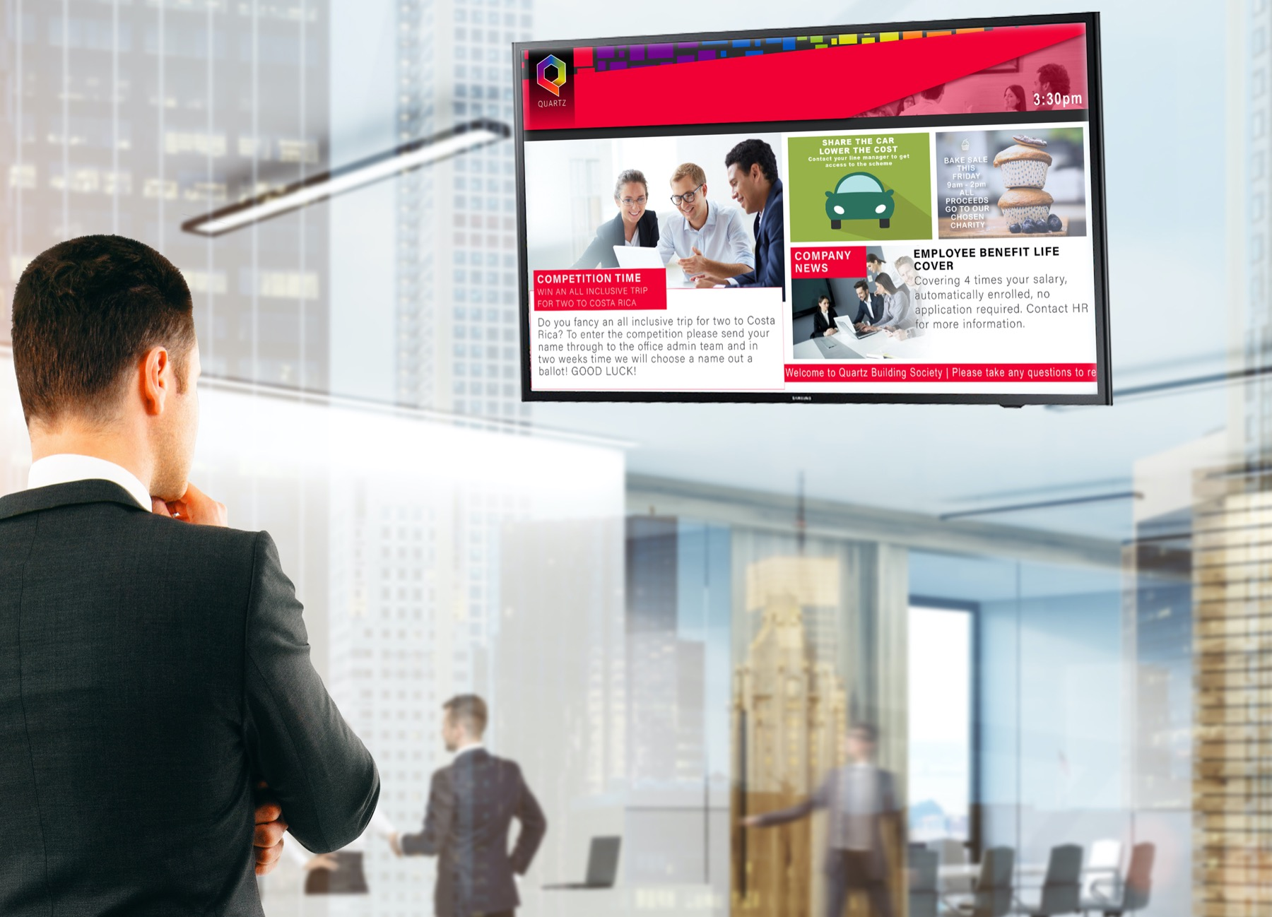 man in suit looking digital signage tv mounted on a wall in a lobby room